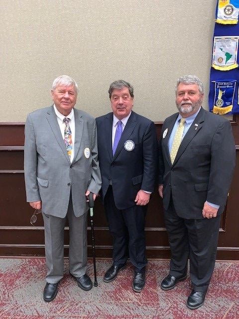 Ken Vaughan (at right) standing with fellow Rotarians